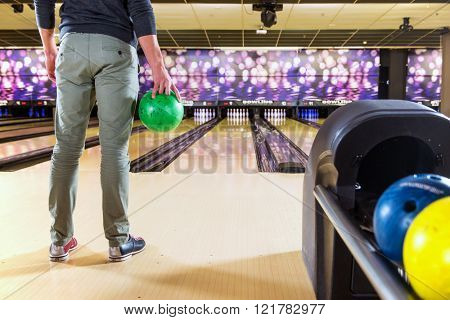 Recreational bowler with a ball in his hand waiting to take his turn and throw the ball at the 10-pins on a bowling alley