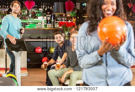 four friends  during a night out at a bowling alley, enjoying themselves in a competitive and active way, having fun, whilst one of them is ready to strike and throw the ball.