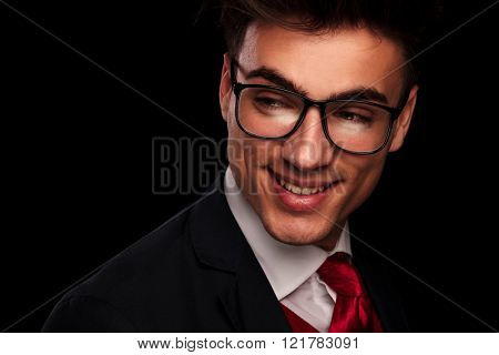close portrait of handsome young man wearing glasses, looking away from the camera while smiling in dark studio background