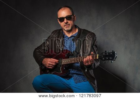 portrait of seated mature rocker in leather jacket playing electric guitar while looking at the camera in gray studio background