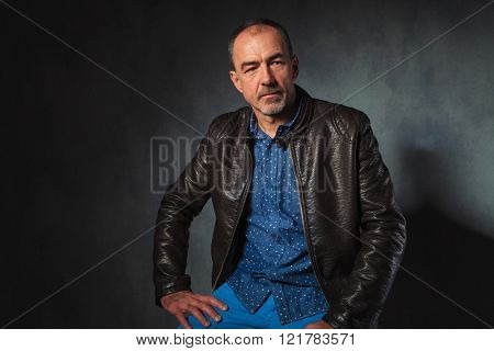 portrait of seated mature man in leather jacket resting his hands while looking away from the camera in gray studio background