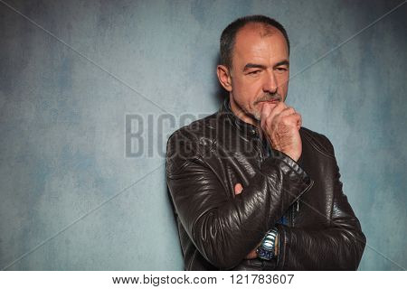 portrait of handsome mature man in leather jacket standing and thinking in gray studio background while looking away from the camera