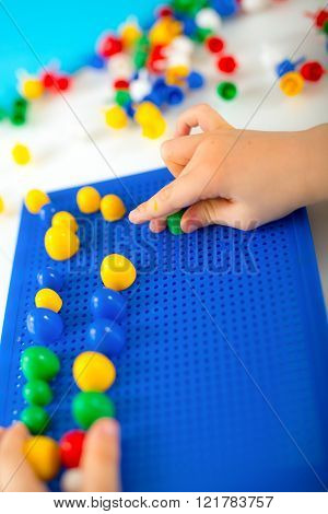 Boy Playing With Educational Toys On A Table