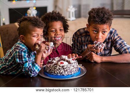 Three kids eating small cake.