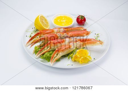 Boiled Crab Claws With Sauce And Lemon On A Plate Over White Background
