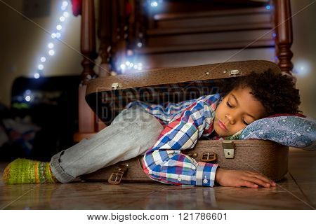 Cute boy sleeps in suitcase.