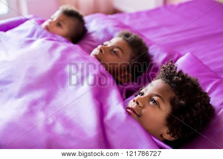 Afro boys on purple bed.