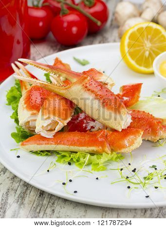Boiled Crab Claws With Sauce , Lemon And Cherry Tomatoe Over Wooden Background