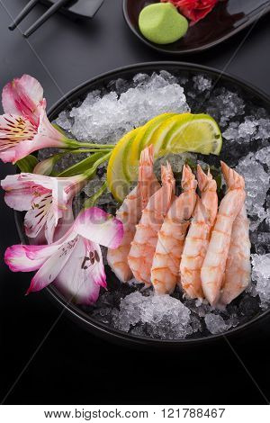 Japanese Cuisine, Shrimp Sashimi With Ice With Ginger And Wasabi On A Black Plate