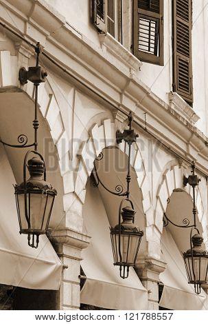 Greece. Corfu (Kerkyra) island. Corfu town. Street lamp detail at an open-air cafe. In sepia toned