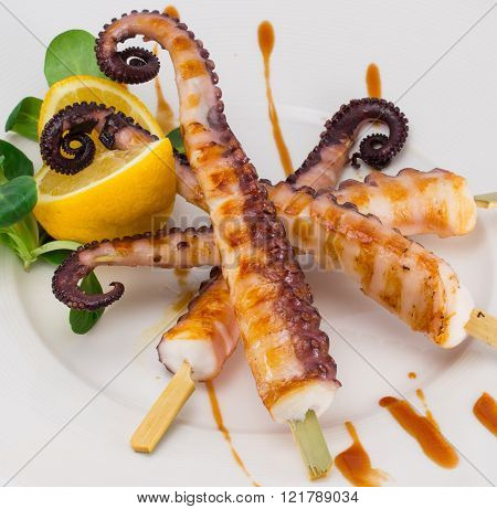 Octopus Skewers With Lemon And Sauce Isolated On White Background