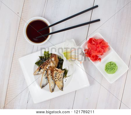 Eel Sashimi With Ginger And Wasabi On A White Plate Over Wooden Background