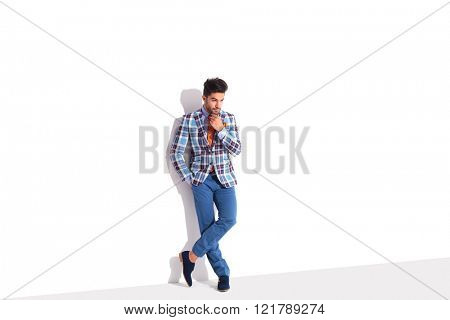young casual man standing in white studio background with hand in pocket while touching his chin. his legs are crossed while looking away from the camera.