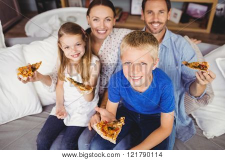 Portrait of smiling family holding pizza slices while sitting on sofa at home