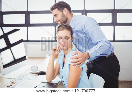 Businessman harassing female colleague at computer desk in office
