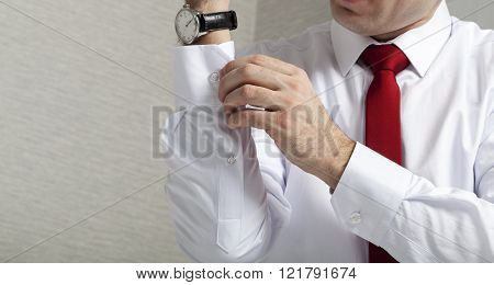 adult man fastens sleeve withe shirts hand