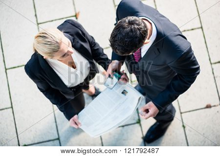 Business man and woman  with newspaper and smart phone standing on square, seen in top view