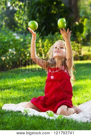 Funny Little Girl With Green Apples