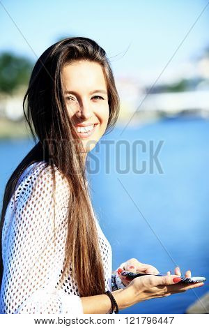Young beautiful woman with smartphone - outdoor portrait