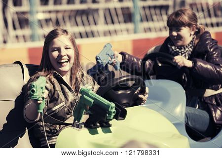 Happy teen girls driving a bumper cars