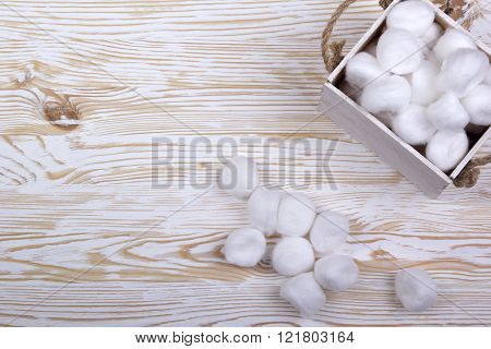 Cotton balls in a box on wooden table