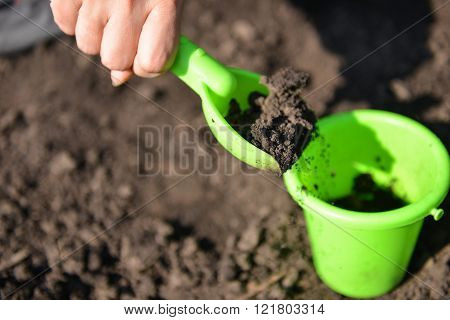 Girl Playing In The Mud With Green Toy Bucket And Spade