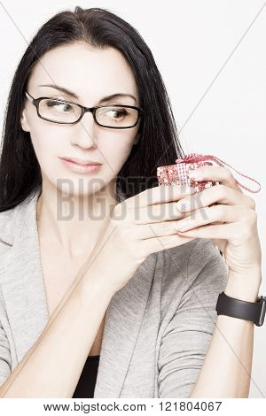 Young woman  holding a red gift box with a surprised delighted expression on her face