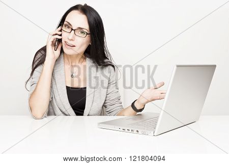 Close up of a young woman working on laptop with office in gray background