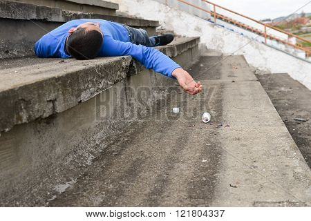 teenager committing suicide with pills. he is lying on the stairs of a stadium with a bottle and pills fallen down. Selective focus