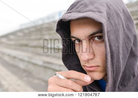 Young Man In Depression Smoking A Cigarette On A Stadion And Looking At The Camera
