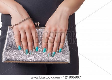 Female Hands With Blue Manicure Holding A Silver Handbag