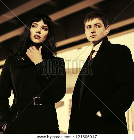 Young fashion man and woman walking on city street