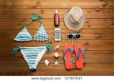 vacation, travel, tourism, technology and objects concept - close up of smartphone and beach stuff