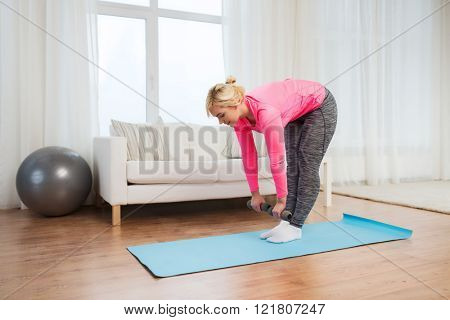 fitness, sport, training and lifestyle concept - smiling woman with dumbbells exercising and doing lean at home