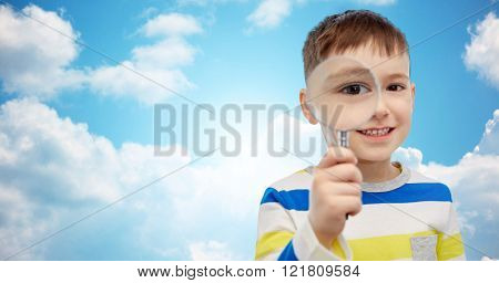 childhood, investigation, discovery, vision and people concept - happy little boy looking through magnifying glass over blue sky and clouds background