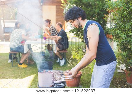 Man cooking meat on the barbecue. He and the friends of him on background are all on late twenties. They are eating outdoor on the grass. Everybody is wearing summer clothes.