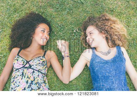 Two Beautiful Women Lying On The Grass