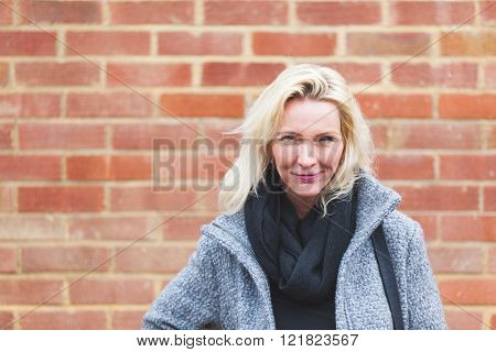 Portrait of a beautiful blonde woman posing against a brick wall. She is looking at camera and smiling. She wears a coat and a scarf. Determination and self confidence concepts.