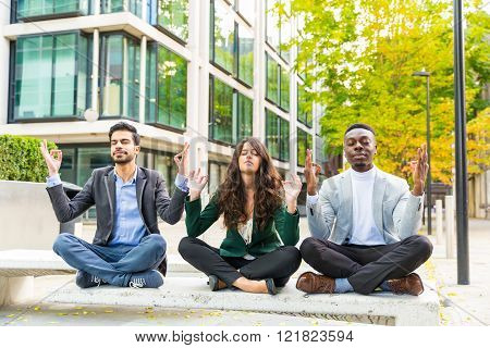 Three young business people doing yoga excercises during a break. They are two men and a woman mixed races sitting on a bench with modern buildings on background. Work stress and business concepts