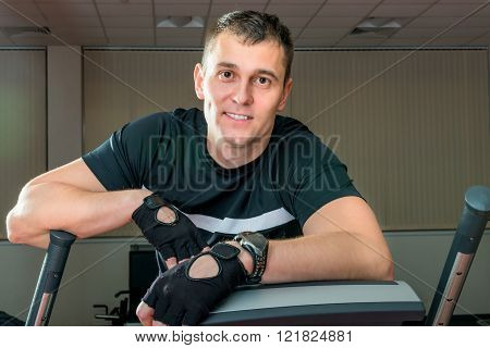 strong young man at the gym on a simulator posing