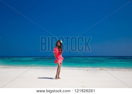 Beautiful woman walking on exotic beach, brunette girl model in red dress on the ocean coast. Vacation. Travel. Bliss freedom concept.