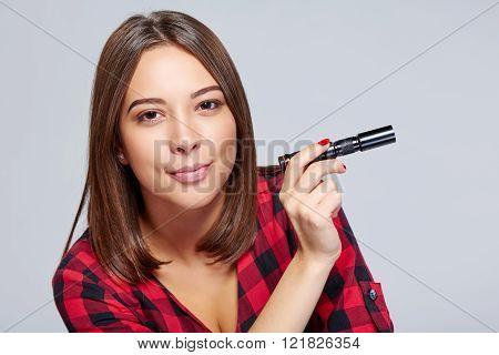 Closeup of smiling female holding pocket flashlight