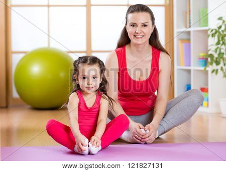 Young mother with little daughter exercising in gym at home