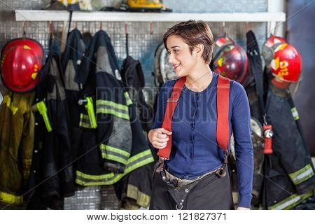 Firefighter Standing Against Uniforms At Fire Station