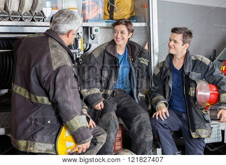 Happy Firefighters Conversing By Firetruck