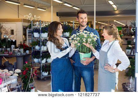 Salesgirls Assisting Male Customer In Buying Flower Plants