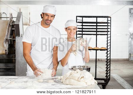 Smiling Baker's Kneading Dough Together In Bakery
