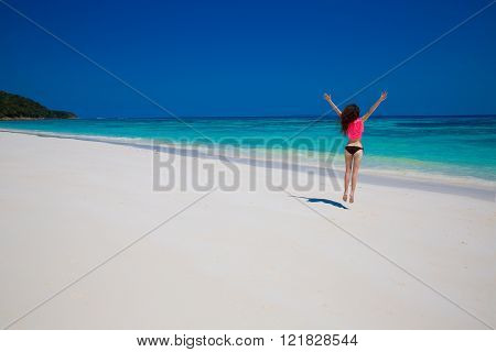 Woman. Happiness bliss freedom beach concept. Enjoyment. Beautiful model jumping on exoptic beach with white sand and blue water. Travel. Free. Vacation.