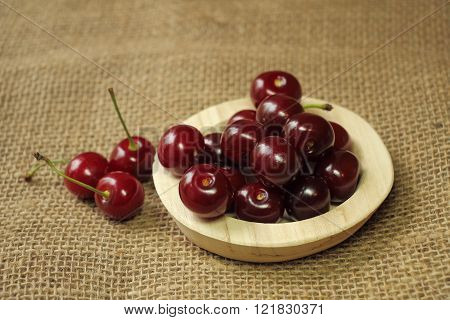 Ripe Cherries On A Wooden Plate.