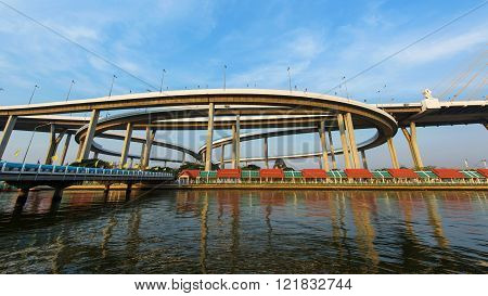 Bhumibol Bridge with skyline reflection against blue sky in Bangkok